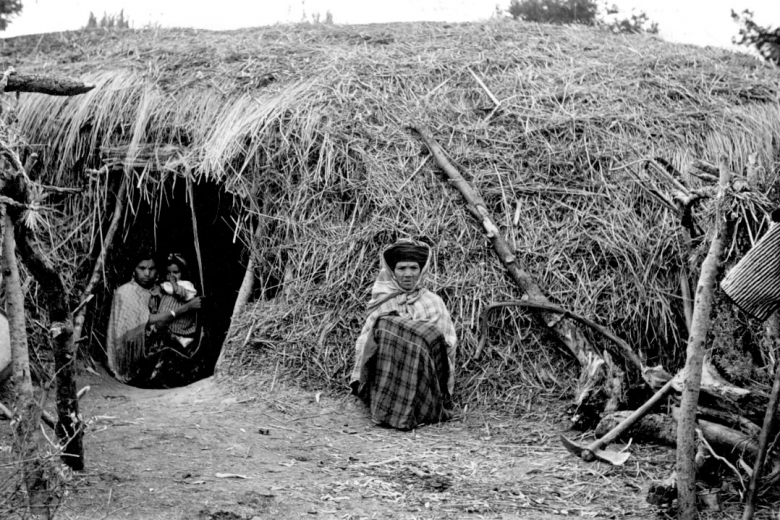 An old woman sits outside a grass-covered building while a woman holds a baby inside the building.