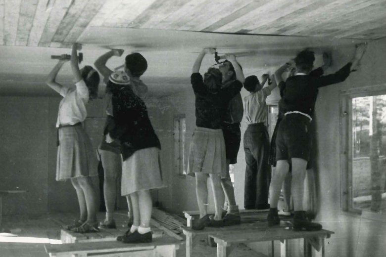Eight young people standing on tables working on the ceiling of a building.