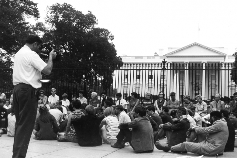 Protesters sit on the sidewalk in front of the White House while a man films.