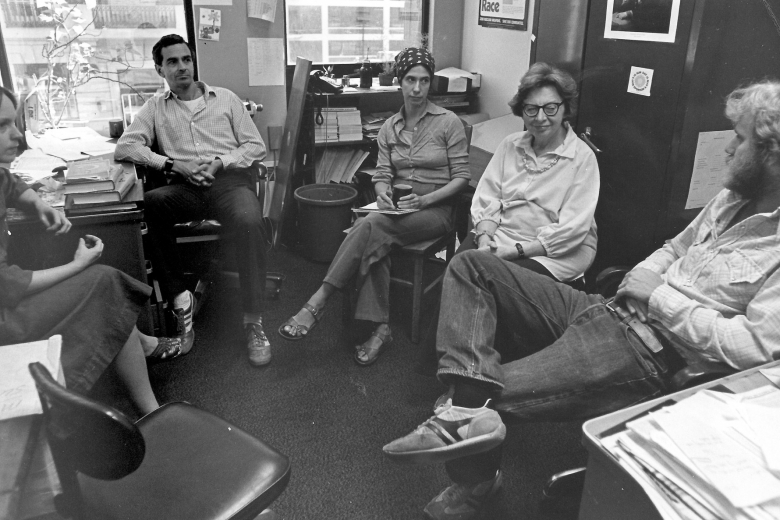 Five people sit in a circle in a small room full of files, talking to one another.