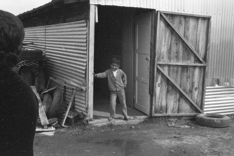 Boy stands in the doorway of a home made out of tin and wood.