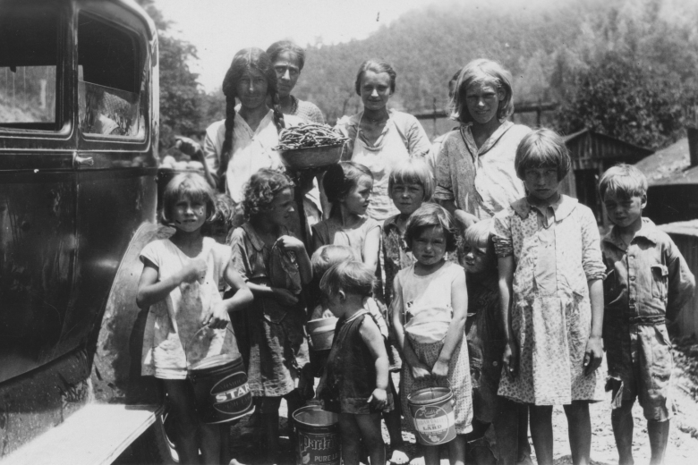 Group of women and children stand next to a car, holding pails.
