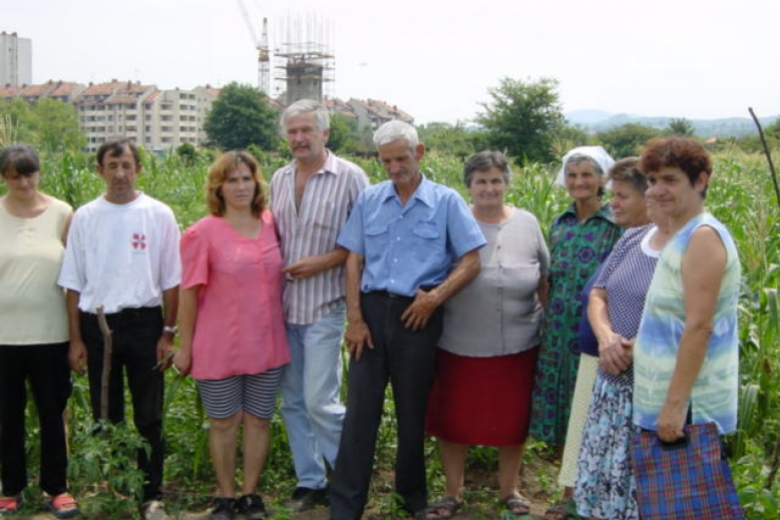 Nine people stand together in a field with buildings in the background.