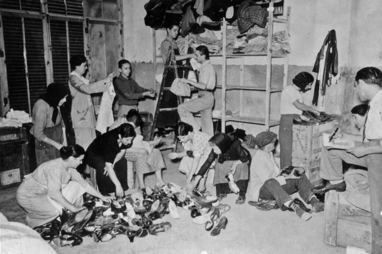 People look at shoes and clothing in large piles in a room.