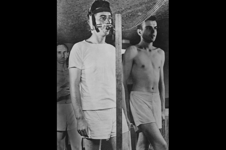 Young adult men standing, one with a tube and equipment attached to his head
