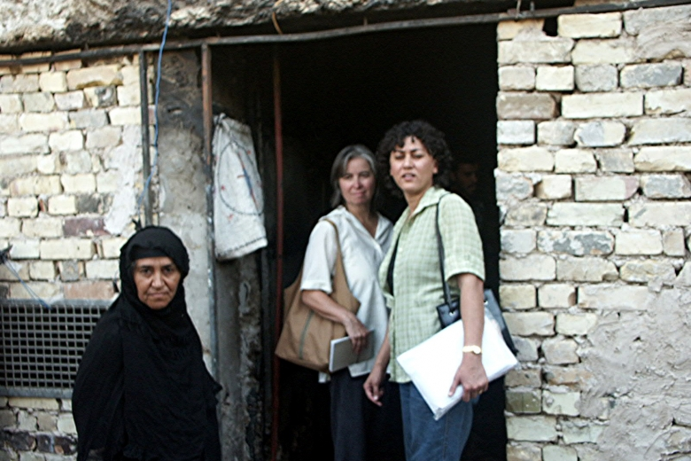 Three women stand together in the doorway of a brick building.