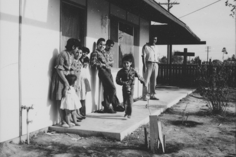 Man and children stand and play on the porch of a house.