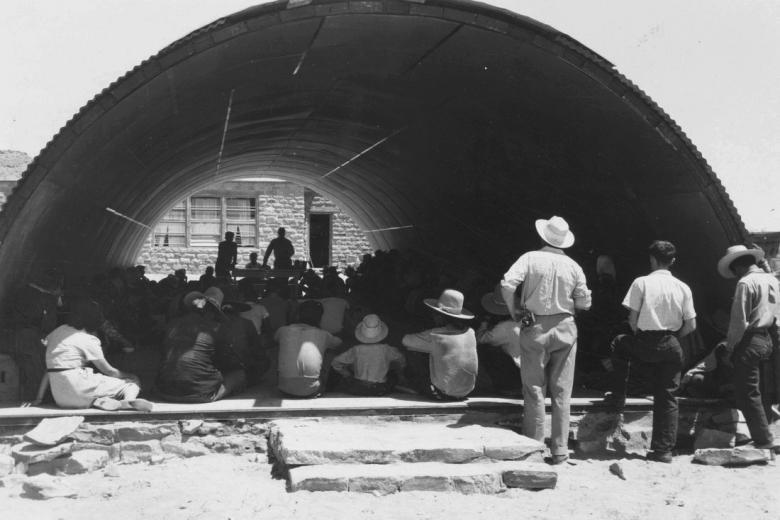 Men watch ceremony with many people inside arched structure