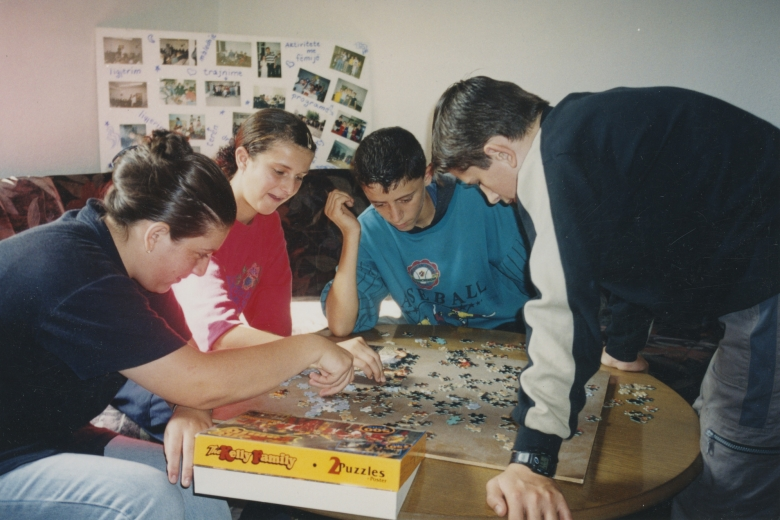 Four children work on a puzzle together.