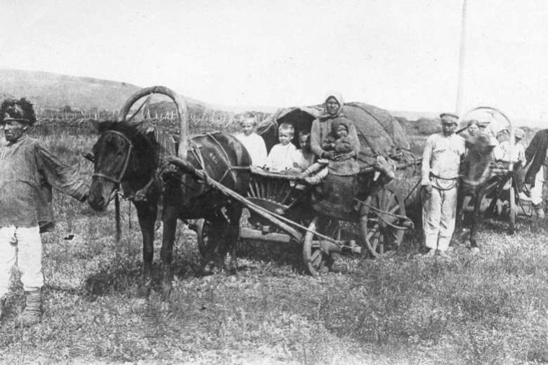 Horse-drawn wagon with men, women, children.