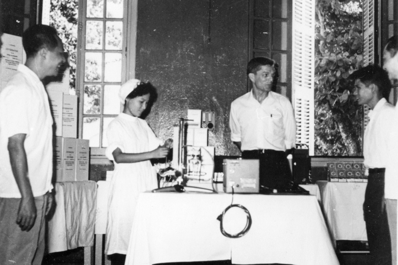 Four people stand together near a table covered with medical equipment.