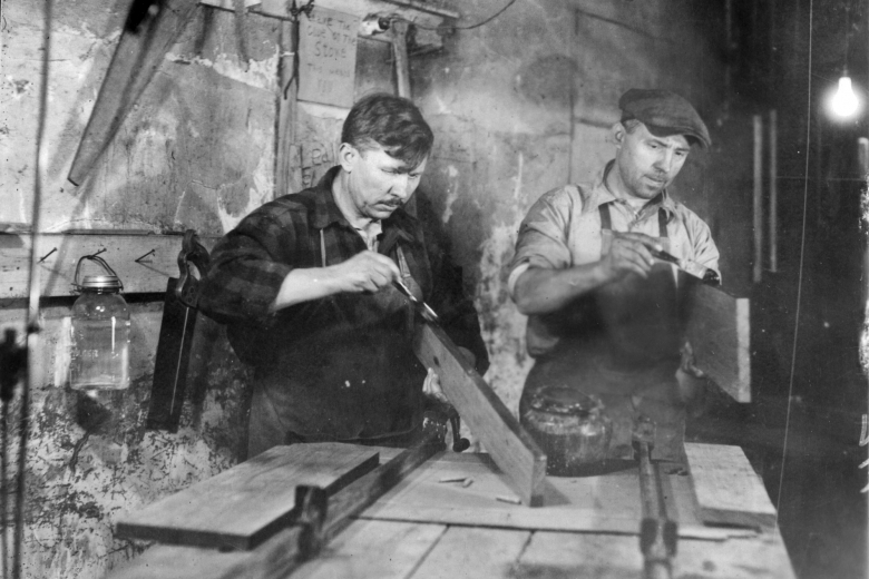 Two men in a workshop do woodworking