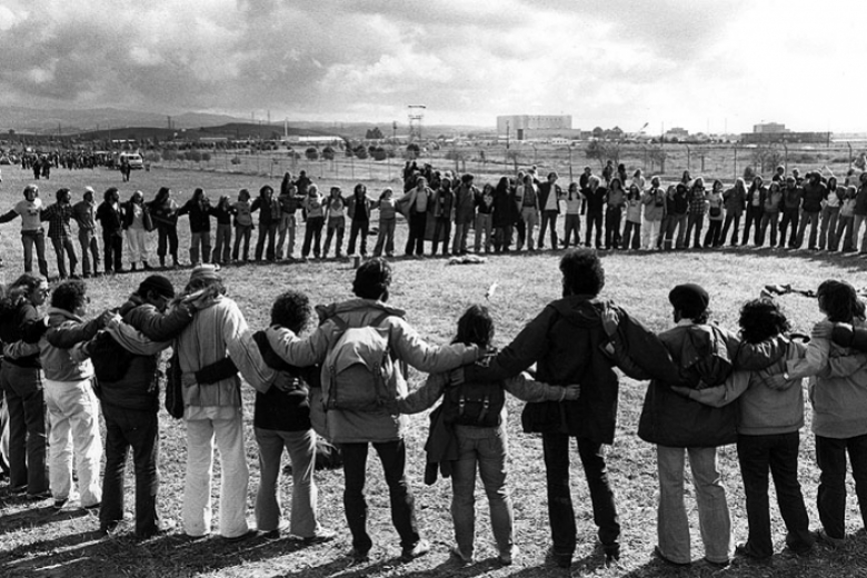 Circle of protesters with arms wrapped around one another, standing in a field.