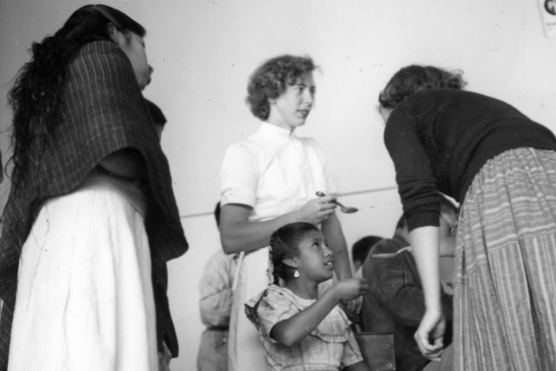 A young woman holding a spoon standing over a young girl, talking with two other young women.