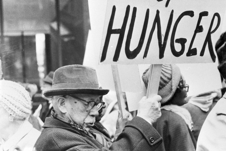Man stands in a crowd of demonstrators, holding a sign.