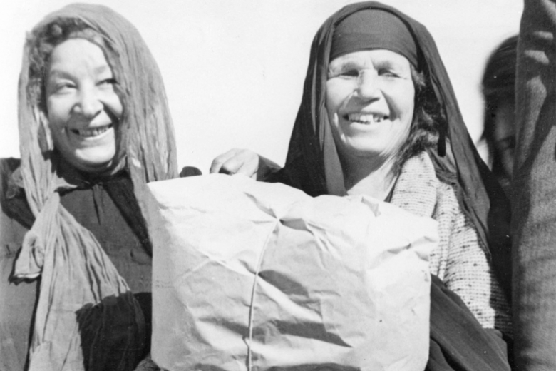 Women hold up bundles of wrapped goods they received.
