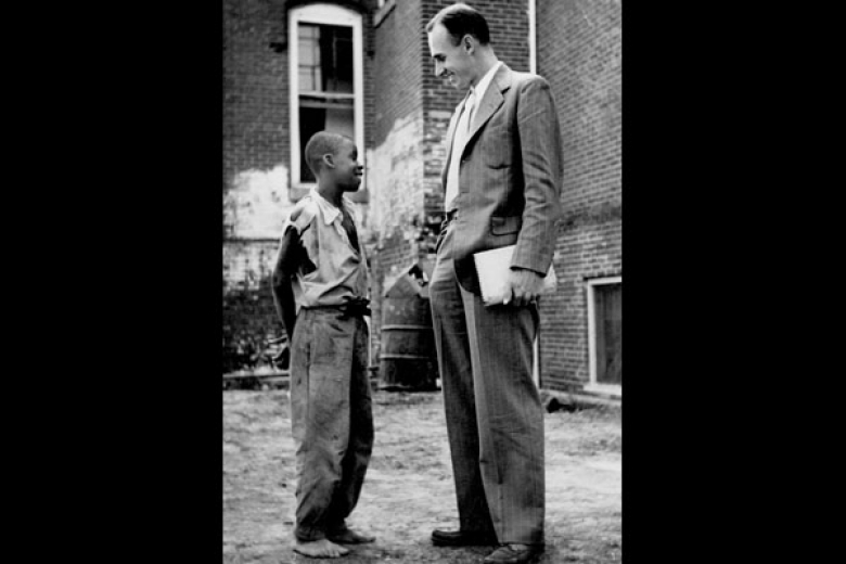 Young child talking with an adult social worker in a suit