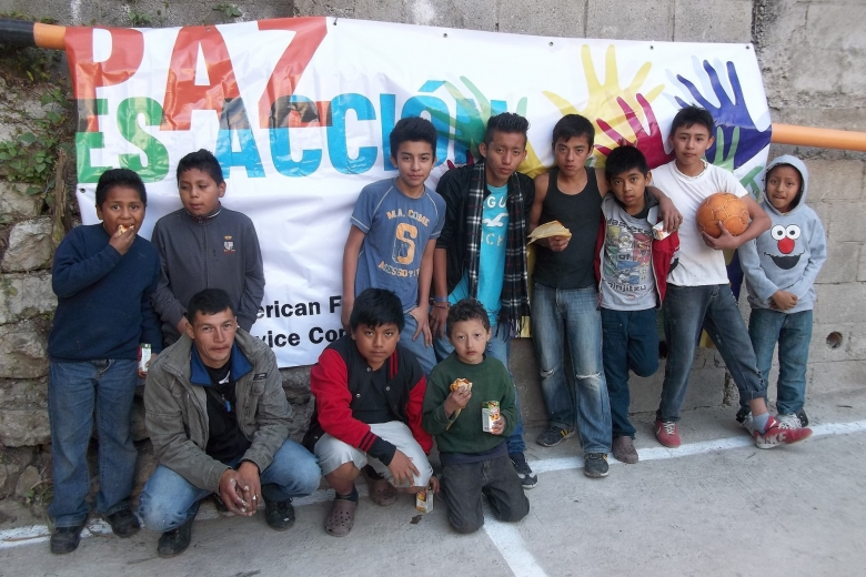 Group of young men stand and squat in front of a banner about peace.
