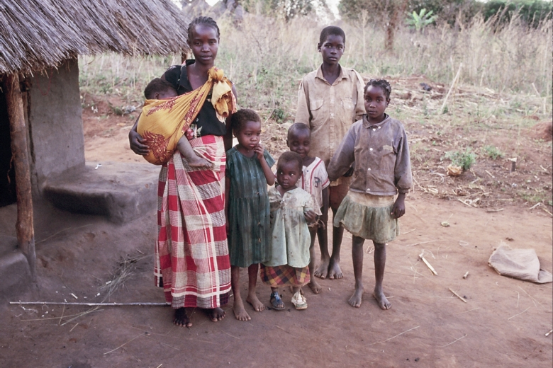 Woman and children stand together outside a house.