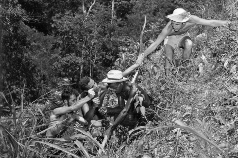 Four young men hold hands and crouch down to form a chain going down a hillside.