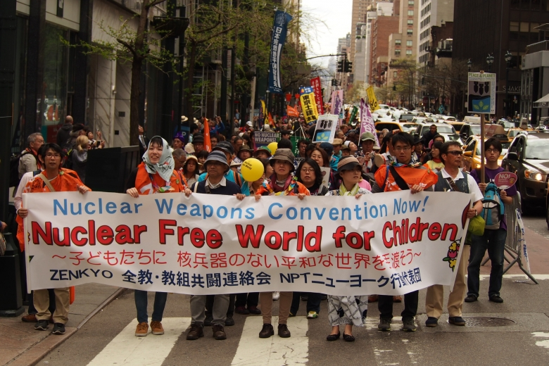 "Group of protesters sanding in a street holding a sign written in both Japanese and English, ""Nuclear weapons convention now! Nuclear free world for children."""