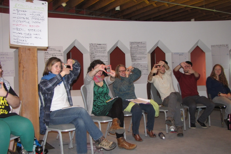 Six young adults sit in chairs and hold their hands up to their heads, forming a rectangle with their fingers.