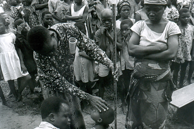 Two people measure the height of a child while a woman looks on.