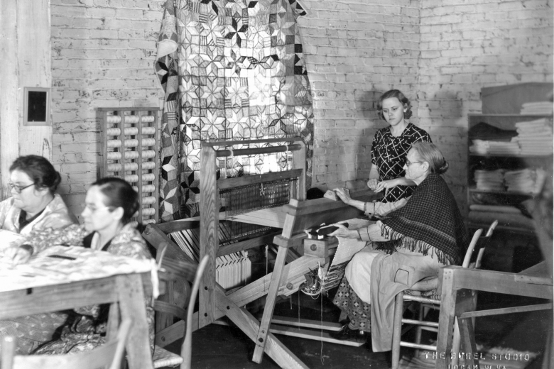 Women of different ages in a sunny workshop with a quilt covering the window