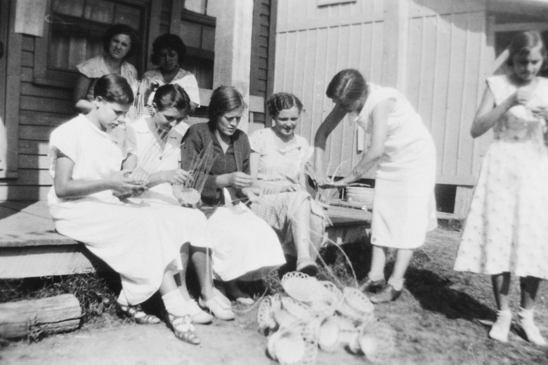 Women sitting on a porch helping each other make baskets