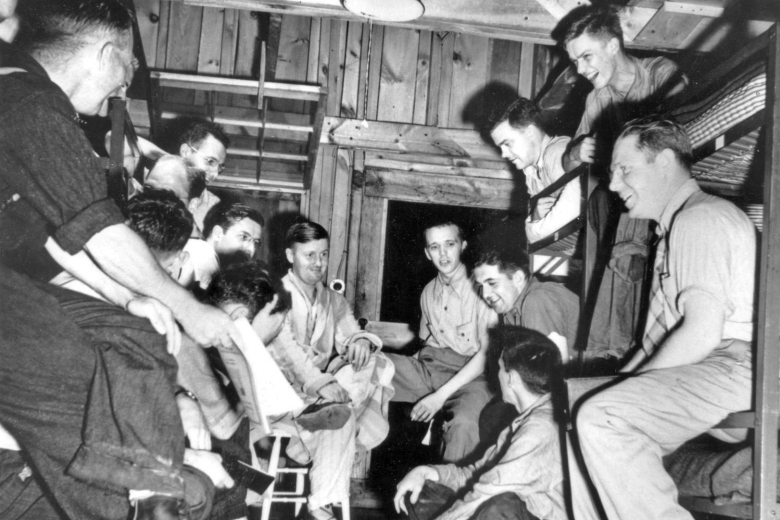 Group of young men talking and laughing inside a wooden building