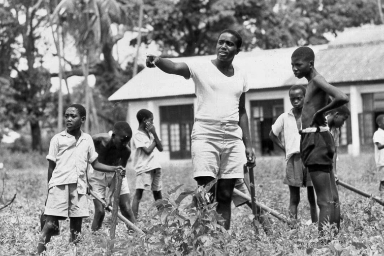 Young man in center of the group points to the left and speaks to group of five children working in a field.