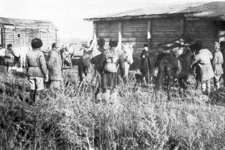 Men wait in line in front of horses and building.