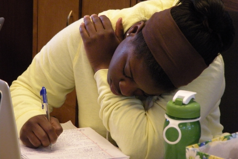 Young woman writes in a notebook.