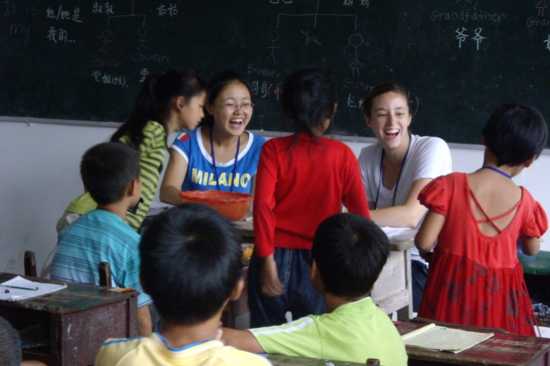 Eight children laugh together in a classroom in front of a blackboard.
