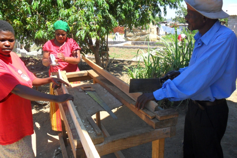 Group of three people do carpentry work in the shade near a tree.