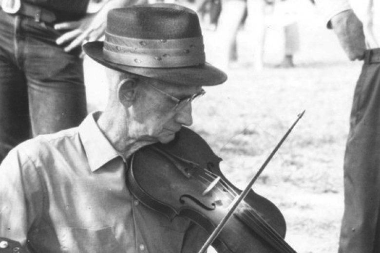 White-haired man plays fiddle