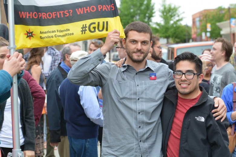 Two men stand in a crowd with a banner to their side.