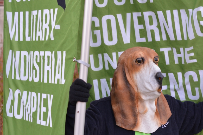 Person wearing dog mask holding a banner.