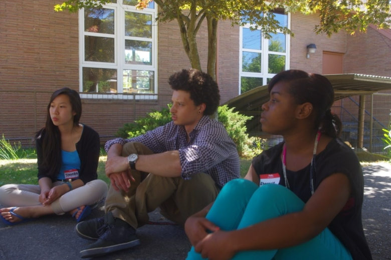 Three young people sit on the ground together.