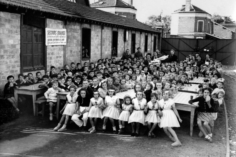 Schoolchildren seated at long tables outside.