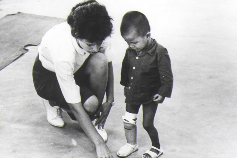 Woman crouching down next to a child with a prosthetic leg.
