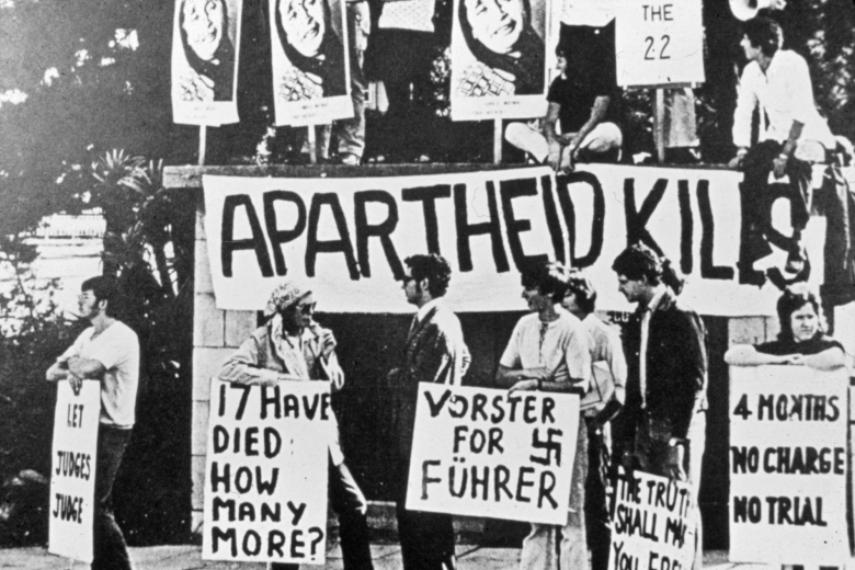 "Group of people holding signs and banners, one of which reads ""Apartheid kills."""