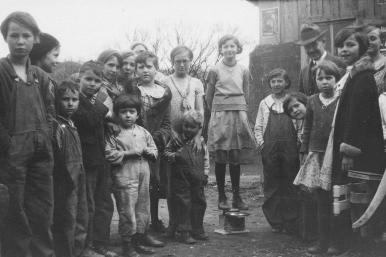 Group of children stand together outside.