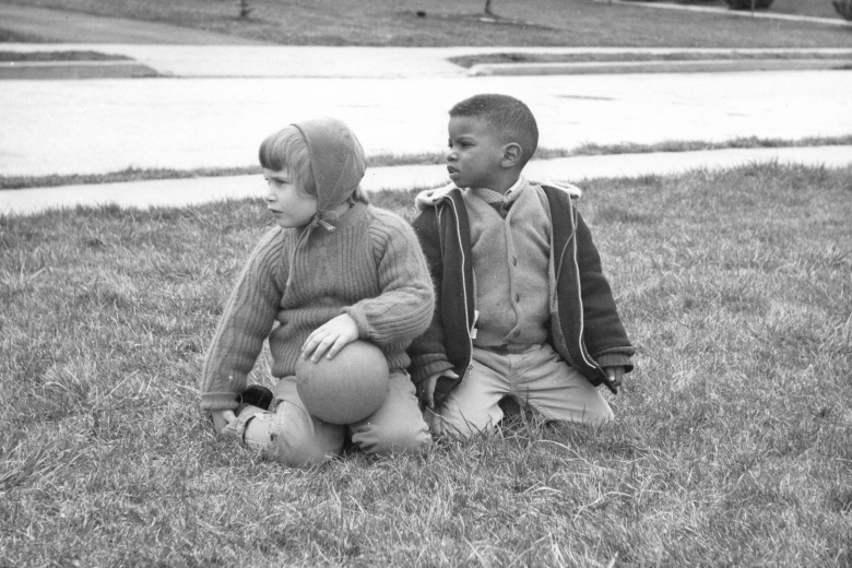 Two children sit together on a lawn.