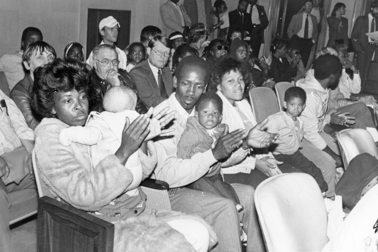 Group of adults and children sit in seats together and clap.