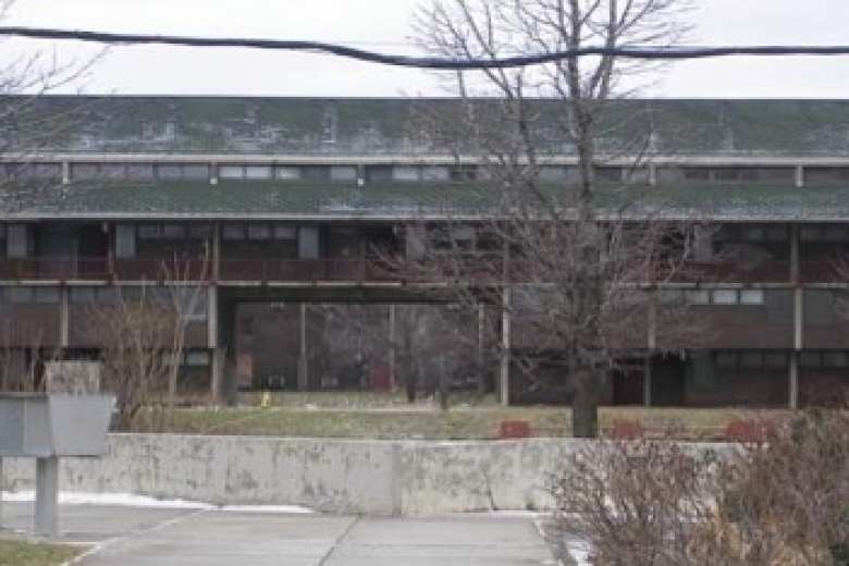 Old, grey building with empty parking lot in front of it.
