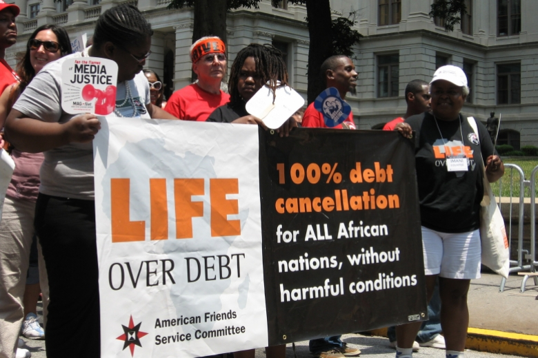 "Group of people walk together, holding a banner that reads ""Life over debt."""