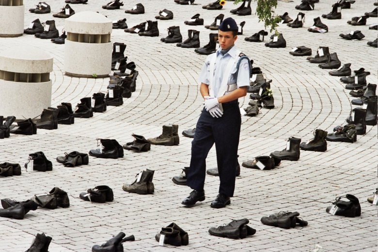 Man wearing military uniform walks among rows of boots.