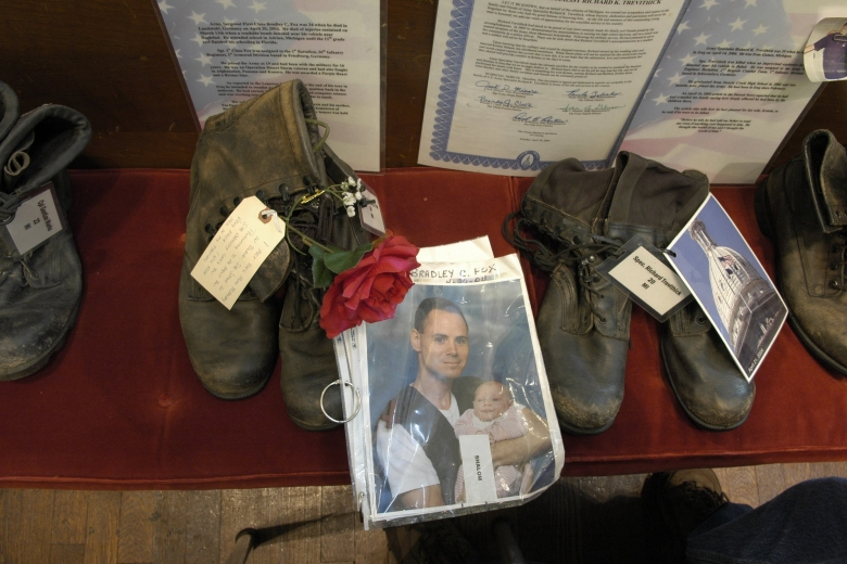 Pairs of boots with photos of servicemen, flowers, and documents.