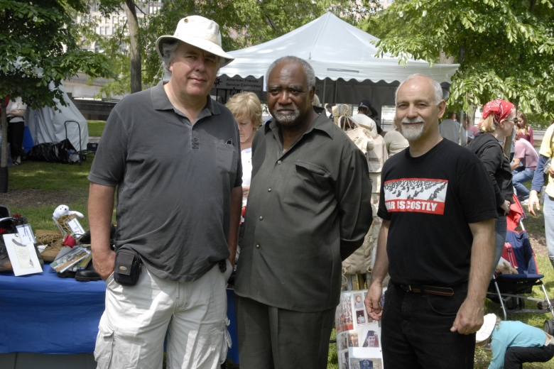 Three men stand next to each other at an outside fair.